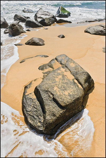 Rock partially covered with sand on a beach in Sanya, Hainan