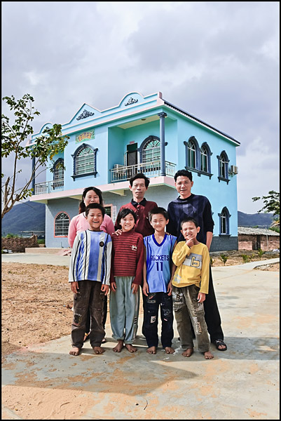 Family posing in front of their house