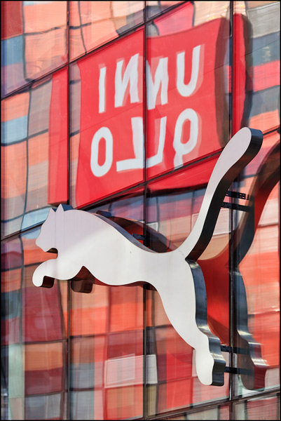 Uniqlo logo reflected in glass surface Puma store